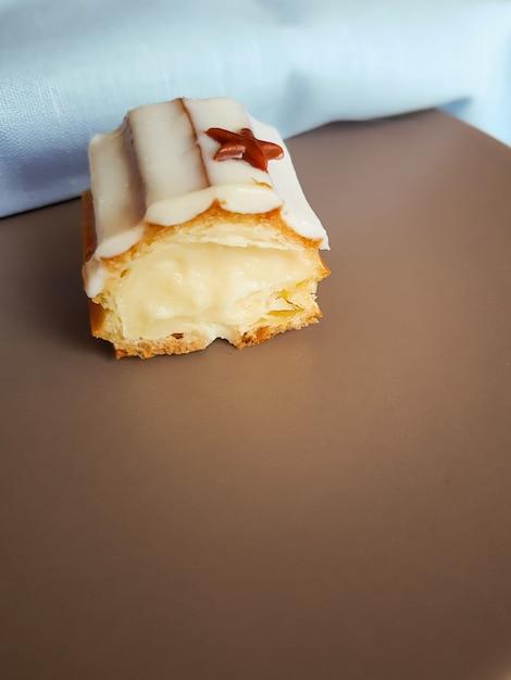 バニラクリームとエクレアのカットは茶色のプレートに白いチョコレート艶出しで覆われています。 Premium写真