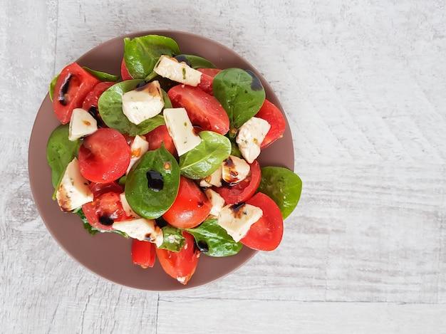 トマト、ほうれん草、モッツァレラチーズのサラダの平面図です。 Premium写真