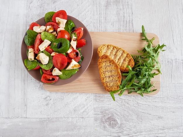 トマト、ほうれん草、モッツァレラチーズとブルスケッタのサラダの平面図です。 Premium写真