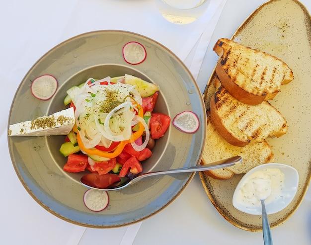 グレープレートにトマト、きゅうり、白ねぎ、大根、オリーブ、フェタチーズのサラダ。 Premium写真