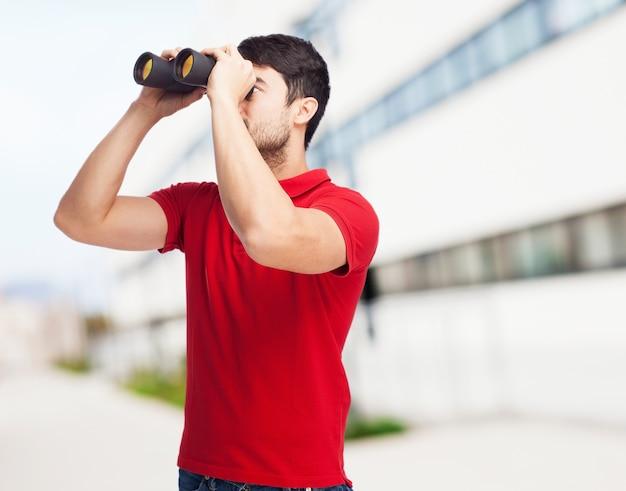 Молодой человек, используя свой бинокль Бесплатные Фотографии