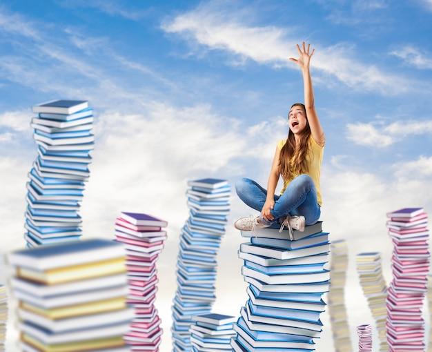 Молодая женщина пытается достичь чего-то сидит на башне книг Бесплатные Фотографии