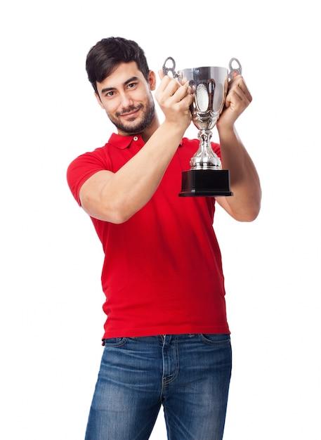 Гордый подросток держит серебряный кубок Бесплатные Фотографии