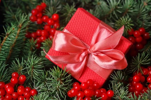 赤い果実で飾られたクリスマスツリーの針に浸したサテンピンクの弓と赤いプレゼントギフトボックス。 Premium写真
