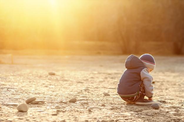 Шестилетний мальчик с аутизмом сидит на земле один на закате. Premium Фотографии