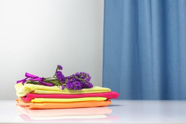 鮮やかな色の純粋な香りのランドリー服が積み重ねられています Premium写真