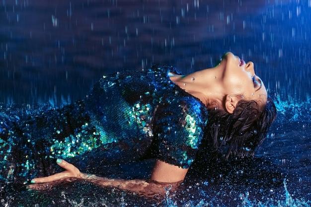 水のスタジオで濡れた床に横になっている魚の鱗に似たスパンコールで輝くドレスを着ているセクシーな女性。 Premium写真