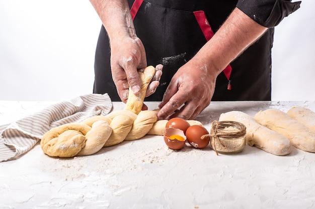 Мужской пекарь, делая традиционный халы еврейский хлеб. приготовление шаг Premium Фотографии