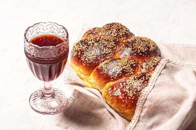 Шаббат или субботняя церемония кидуша. хлеб халы, бокал красного кошерного вина Premium Фотографии