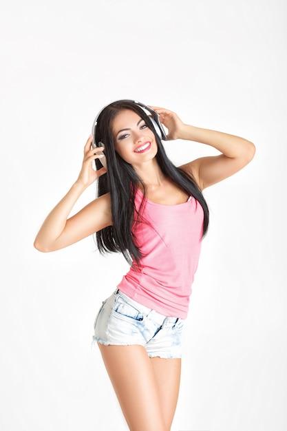 音楽を聴くヘッドフォンを持つ若い女 Premium写真