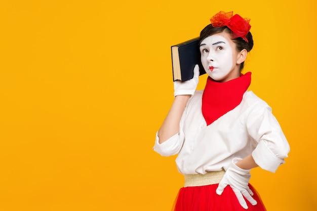 本とパントマイムの女性アーティストの肖像画 Premium写真