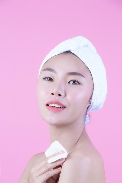 アジアの美しい女性がピンクの背景、美容とスパで顔を拭きます。 無料写真