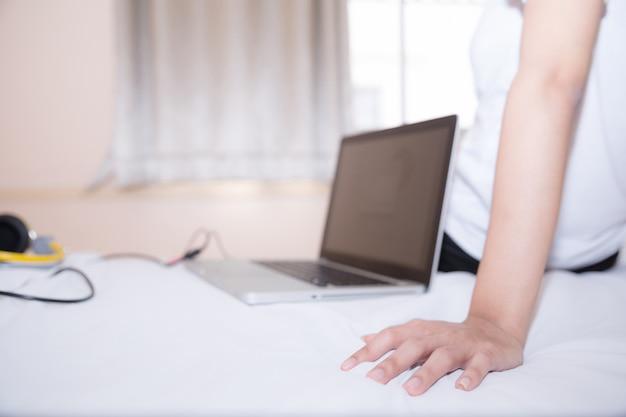 スポーティなパジャマを着ている女性は、座っているか、友人とオンラインでチャットしたり、オンラインで買い物をしたりします。そして休日にはベッドでリラックスしてください。 無料写真