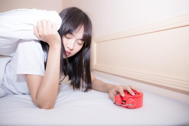 Молодая спящая женщина и будильник в спальне у себя дома Бесплатные Фотографии