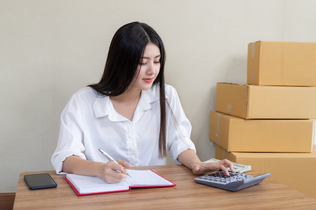 美しいアジアのビジネスの若い女性は商品を注文した後幸せになりました 無料写真
