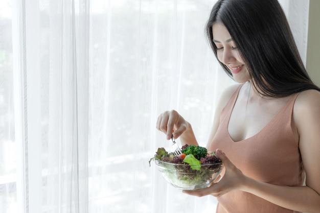 美しい美しさの女性アジアのかわいい女の子は健康的な朝のダイエット食品新鮮なサラダを食べて幸せを感じる 無料写真