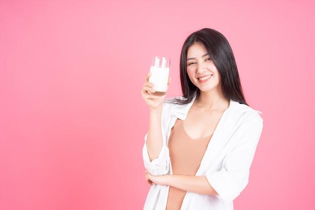 アジアのかわいい女の子の美しさの女性はピンクの背景に朝の健康のために牛乳を飲んで幸せを感じる 無料写真
