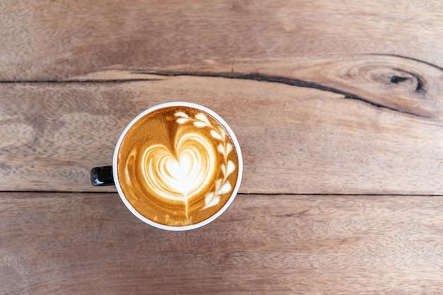 コピースペースを持つ木製のテーブル背景にカップのホットアートコーヒーカプチーノ 無料写真