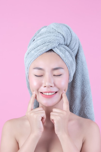 清潔でさわやかな肌を持つ若い女性アジアが自分の顔に触れる 無料写真
