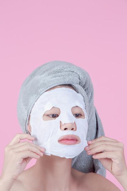 美しいアジアの女性は、ピンクの背景のシートにフェイスマスクを使用しています。 無料写真