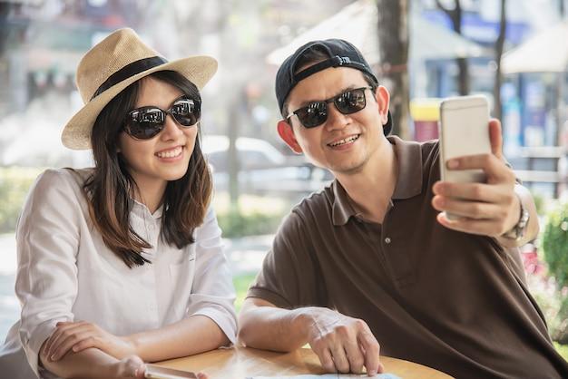 Азиатская пара любит путешествовать сидя в кафе Бесплатные Фотографии