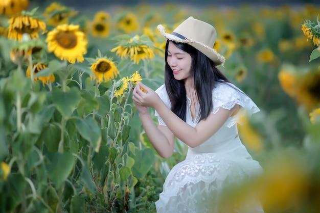 ヒマワリ、健康的なライフスタイルのフィールド上の白いドレスで美しいセクシーな女性 無料写真