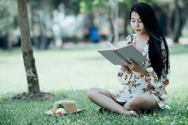 Красивая девушка читает книгу в парке в летнем солнечном свете Бесплатные Фотографии