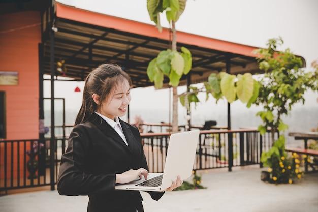 コーヒーを飲みながら、木製のテーブルでコーヒーショップに座っている若い女性。テーブルの上はノートパソコンです。 無料写真