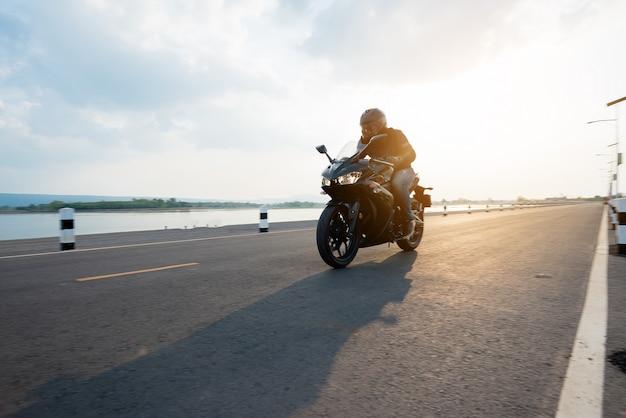 Наездник на мотоцикле по дороге катается. весело проводя время на пустой дороге Бесплатные Фотографии
