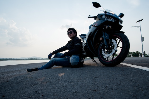 Красивый мотоциклист с шлемом в руках мотоцикла Бесплатные Фотографии
