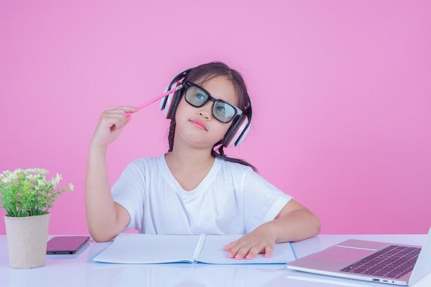 女の子はピンク色の背景に本を書きます。 無料写真