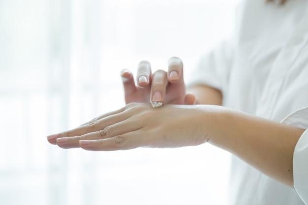 女性は彼女の手に化粧品クリームの瓶を保持します。 無料写真