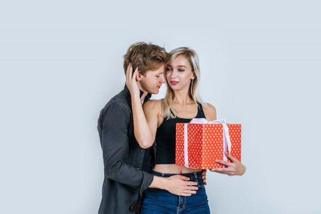 Портрет счастливой молодой пары любят вместе сюрприз с подарочной коробке Бесплатные Фотографии