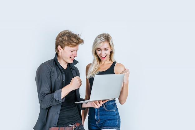 Портрет счастливой молодой пары с помощью портативного компьютера Бесплатные Фотографии