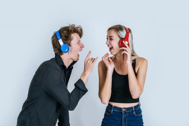 音楽を聞くヘッドフォンで幸せな若いカップル 無料写真