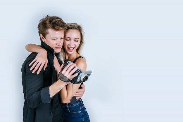 ビデオカメラとレコードクリップビデオを保持しているカップルの幸せな肖像画 無料写真