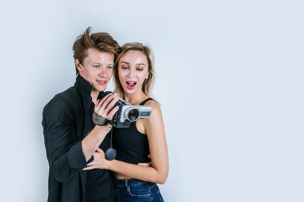 Счастливый портрет пары, держащей видеокамеру и запись клипа Бесплатные Фотографии