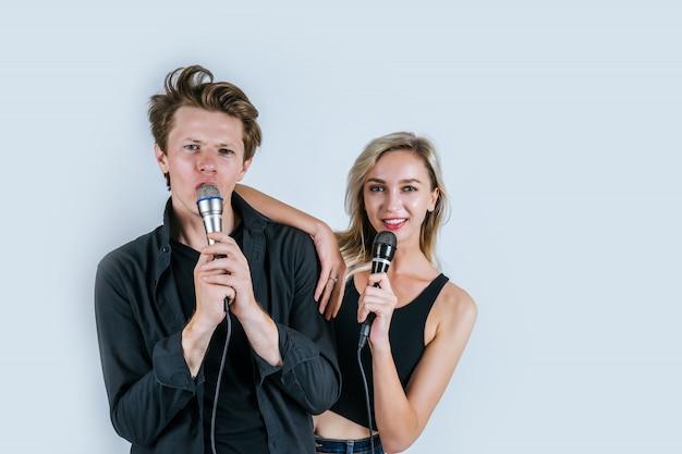 Счастливый портрет пары, держащей микрофон и поют песню Бесплатные Фотографии