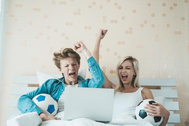 幸せなカップルがベッドの上にサッカーを見て 無料写真