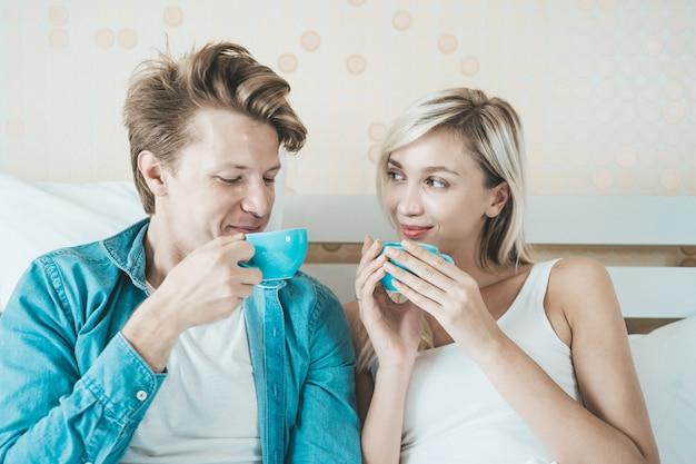 幸せなカップルの手持ち株カップと朝のコーヒーを飲む 無料写真