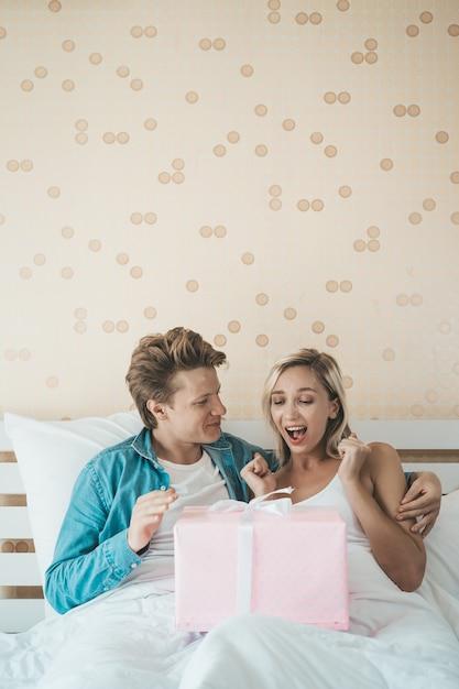 ボーイフレンドはベッドの上のギフトボックスと彼のガールフレンドを驚かせる 無料写真