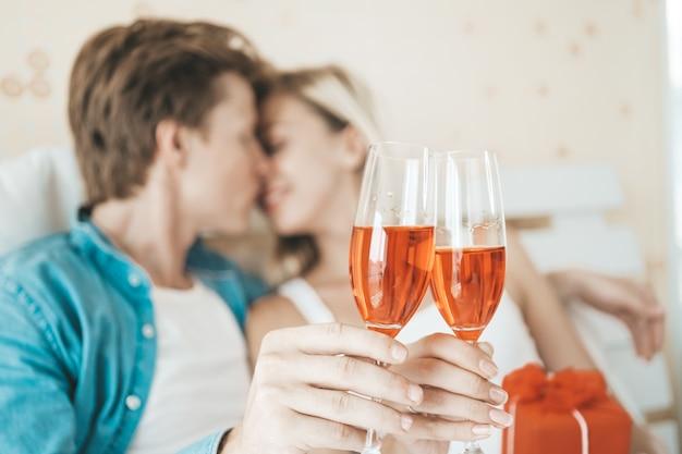 幸せなカップルの寝室でワインを飲む 無料写真