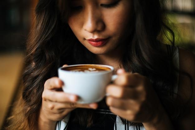笑みを浮かべて肖像画アジア女性のコーヒーショップカフェでリラックス 無料写真