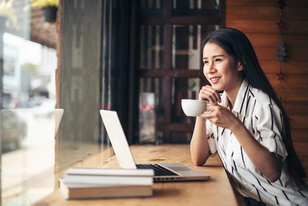コーヒーショップカフェでラップトップコンピューターで働く美しい女性 無料写真