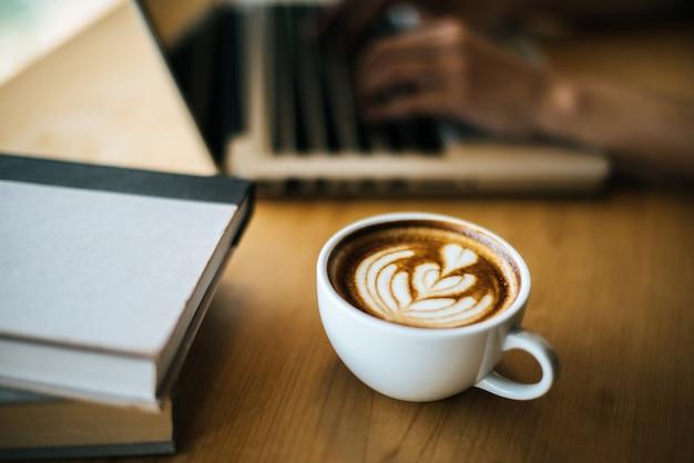 Латте арт в чашке кофе на столике в кафе Бесплатные Фотографии