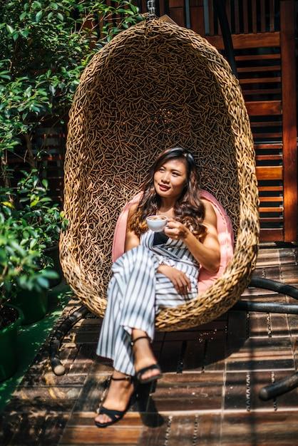 美しいアジアの女性の肖像画はカフェでリラックス 無料写真