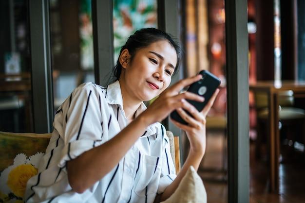 女性が座っているとカフェで彼女のスマートフォンをプレイ 無料写真