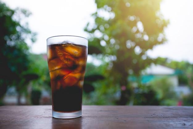 テーブルの上の氷とコーラのガラス。 無料写真