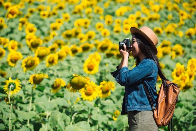 女の子はひまわり畑で写真を撮って幸せです。 無料写真