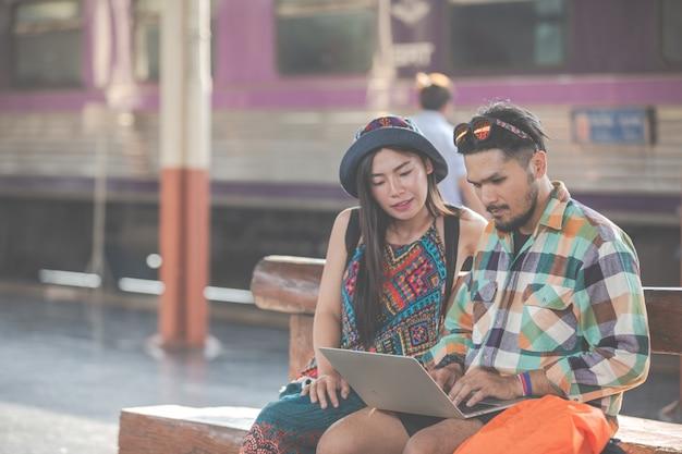 観光客、観光スポットを見つけるためにタブレットを見ているカップル。 無料写真